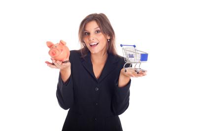 Junge Geschäftsfrau mit Einkaufswagen und Sparschwein